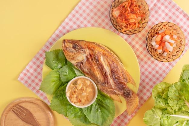 Gebratener fisch auf einem teller mit gemüse serviert