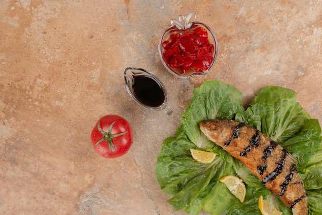 Gebratener fisch auf salat mit zitronenscheiben, gurken und granatapfelsauce.