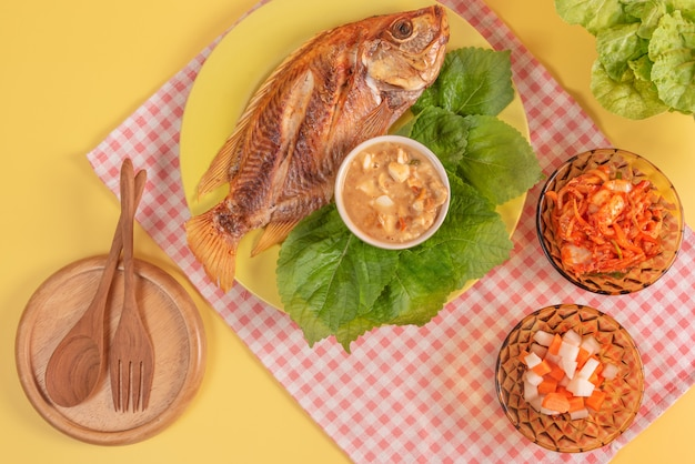Gebratener fisch auf teller serviert eingelegtes gemüse und frische grüne blätter