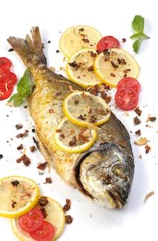 Gebratener fisch dorado mit zitronenscheiben und gewürzen mit tomatengeschmack