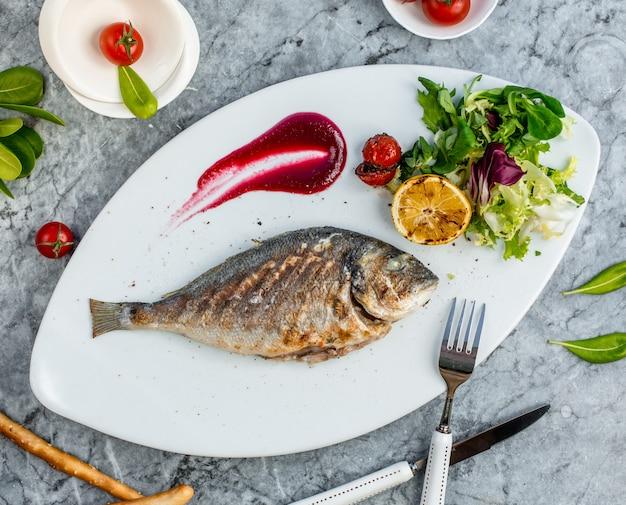 Gebratener fisch mit gemüse in der platte 4