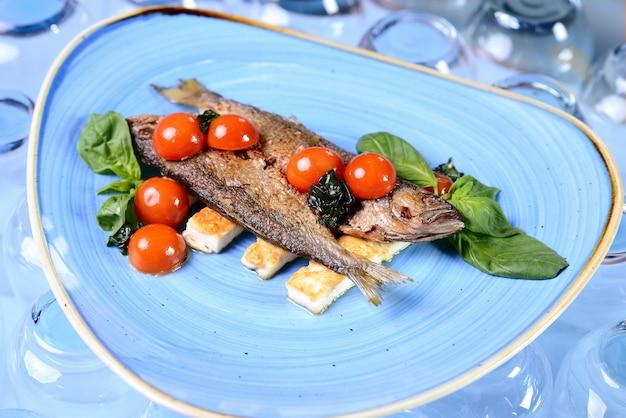 Gebratener fisch mit gemüse und basilikum