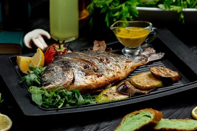 Gebratener fisch mit kartoffeln auf ofenbrett