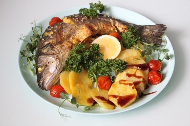Gebratener fisch mit kartoffeln und verziert mit salat und zitrone auf hellem hintergrund