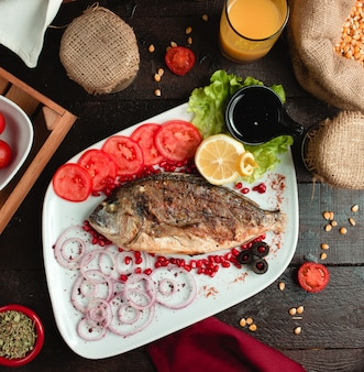 Gebratener fisch mit tomaten und zwiebeln