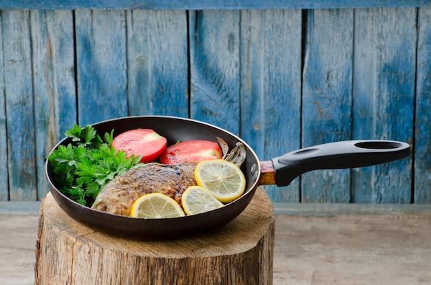 Gebratener fisch mit zitrone und tomaten in einer pfanne auf einem baumstumpf