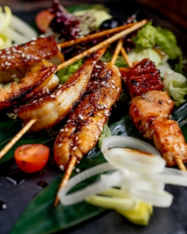 Gebratener fisch und garnelen auf stangen, serviert mit salattomaten und zwiebeln