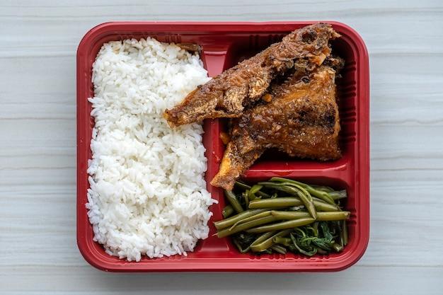 Gebratener fisch und gekochter reis und grüne kräuter in einem behälter, nahaufnahme, draufsicht. street food in vietnam