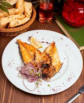 Gebratener, gegrillter fisch serviert in weißen teller mit zwiebelsalat, zitrone und kräutern