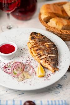 Gebratener gegrillter fisch, serviert mit kräutern, zitrone, zwiebelsalat und diproter tomatensauce.