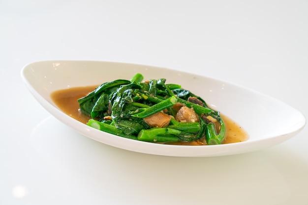Gebratener gesalzener fisch mit chinesischem grünkohl - asiatische küche