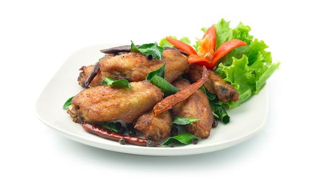 Gebratener hühnerflügel mit getrocknetem chili aus thailändischen kräutern