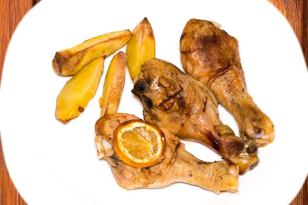 Gebratener hühnerkeulenstock mit kartoffeln auf platte über hölzernem hintergrund, draufsicht.