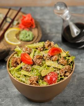Gebratener hühnersalat mit frischer avocado, salat, tomaten in öl, garniert mit sesam