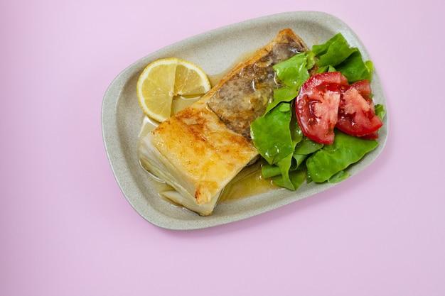 Gebratener kabeljau mit frischem salat auf teller auf rosa