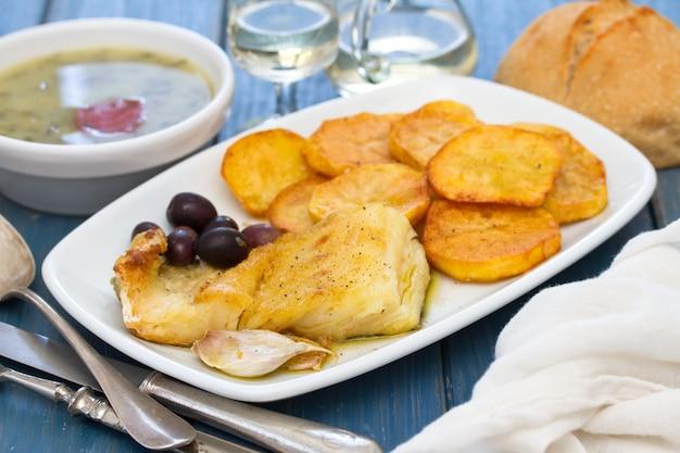 Gebratener kabeljau mit kartoffel auf weißem teller
