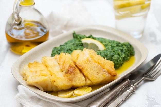 Gebratener kabeljau mit spinat auf teller