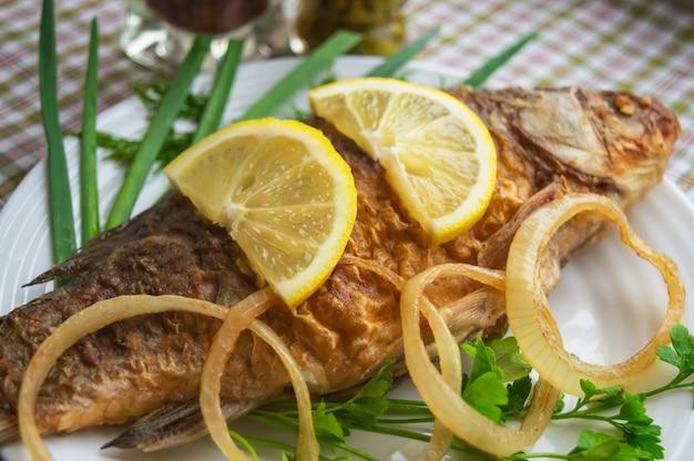 Gebratener karpfenfisch mit gemüse auf einem weißen teller.
