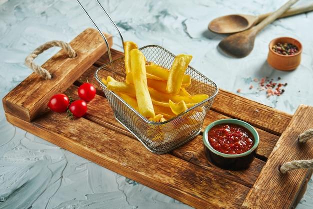 Gebratener kartoffeldip in einem metallkorb auf einem holztablett. leckeres fast food. nahaufnahme ansicht pommes frites