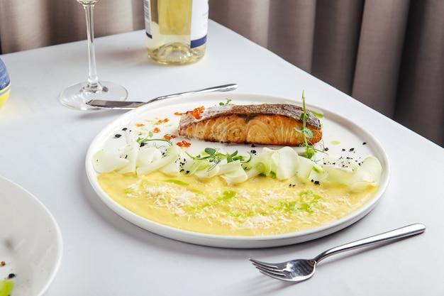 Gebratener lachs mit kartoffelpüree und rotem kaviar auf einem weißen teller
