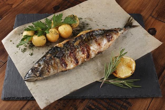 Gebratener makrelenfisch gefüllt mit zitrone. junge kartoffelbällchen auf schieferoberfläche. holzhintergrund