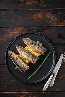 Gebratener makrelenfisch mit dunklem holztisch aus knoblauch, paprika und safran, draufsicht mit kopierraum.