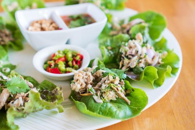 Gebratener makrelensalat mit frischem gemüse, chilischoten, erdnuss und thailändischer würziger fischsauce auf holztisch. dieses essen ist ein traditionelles thailändisches menü namens maing-pla-too. nahansicht