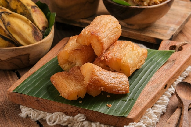 Gebratener maniok wird auf einem schneidebrett mit bananenblattboden serviert. so arrangiert mit einem klassischen küchentisch-thema