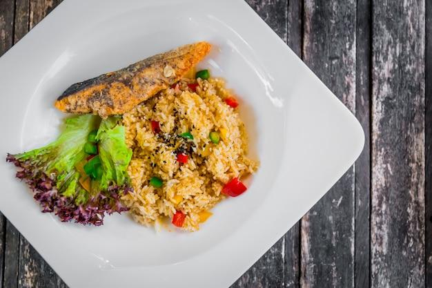 Gebratener reis des gesunden lebensmittels des sauberen lebensmittels kocht mit dem gedienten gemüseindischen sesam und lachsfisch