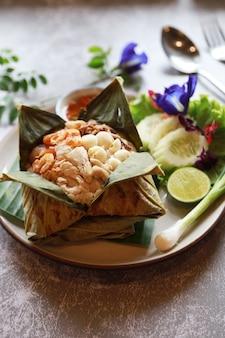 Gebratener reis in pandan-blatt mit gemüse legte es auf weißen teller, beliebtes essen im thailändischen restaurant