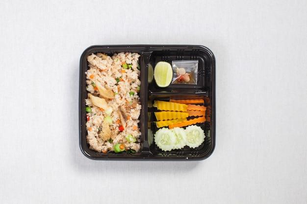 Gebratener reis mit gebratenem fisch in schwarzer plastikbox, auf eine weiße tischdecke, lebensmittelbox, thailändisches essen.