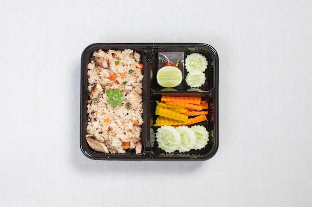 Gebratener reis mit gebratenem thunfisch in schwarzer plastikbox, weiße tischdecke, lebensmittelbox, thailändisches essen.