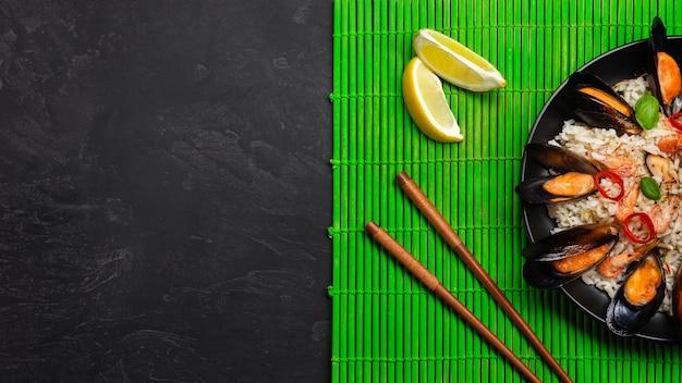 Gebratener reis mit meeresfrüchten, garnelen und basilikum in einem schwarzen teller mit stäbchen auf grüner bambusmatte und steintisch. ansicht von oben.