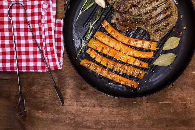 Gebratener rindfleischstapel und -karotten auf einer runden bratpfanne