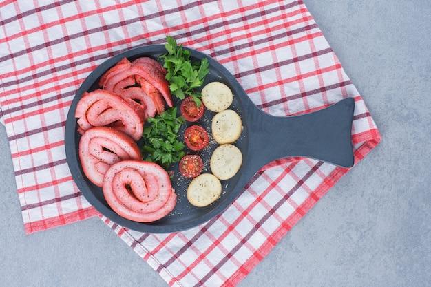 Gebratener speck mit kartoffel auf schwarzer pfanne.