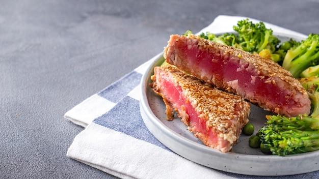 Gebratener thunfisch mit brokkoli und grünen erbsen auf einem teller.