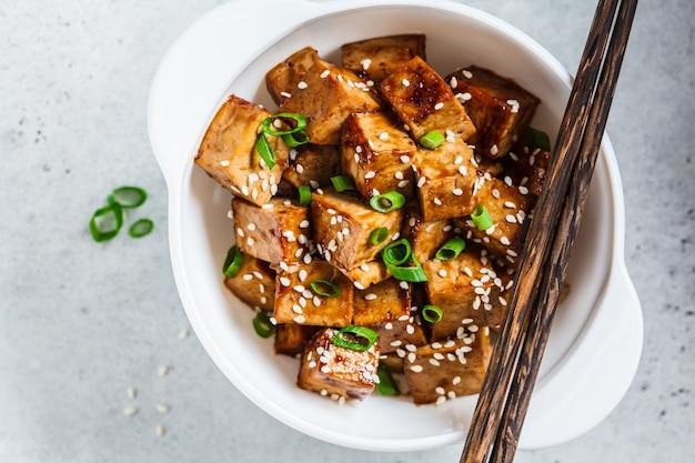 Gebratener tofu in teriyaki-soße in der weißen schüssel, draufsicht. veganes food-konzept.