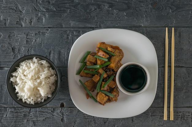 Gebratener tofu mit reis und sojasauce auf einem weißen teller. flach liegen. vegetarisches asiatisches gericht.