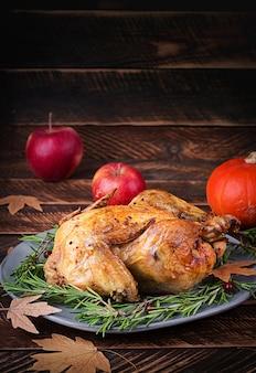Gebratener truthahn, garniert mit preiselbeeren auf einem rustikalen tisch mit kürbissen, äpfeln und herbstblättern. erntedankfest.