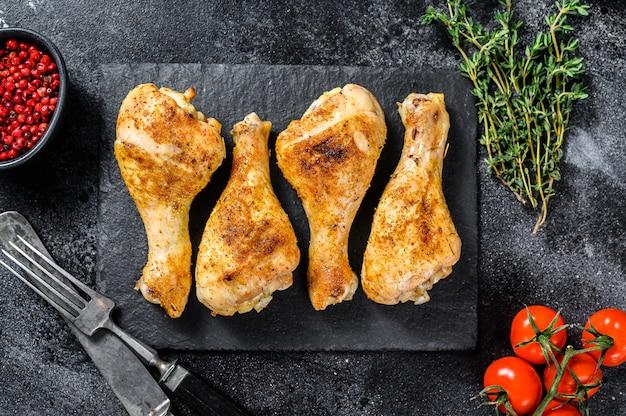 Gebratener würziger hühnertrommelstock, schenkel mit gewürzen und kräutern.