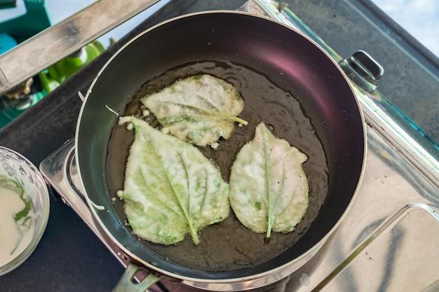 Gebratenes chaplu-blatt (wild betel leafbush) in der pfanne zum essen mit traditionellem thailändischem essen.