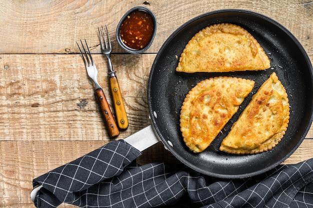 Gebratenes empanadas herzhaftes gebäck mit rindfleischfüllung in einer pfanne
