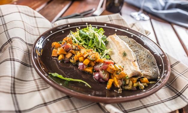 Gebratenes fischfilet mit kürbisstücken und kräuterdekoration im pub oder restaurant.