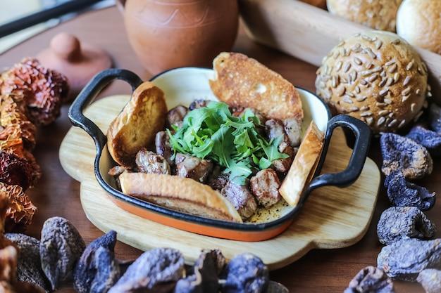 Gebratenes fleisch auf dem holzbrett mit gemüse und brötchen mit sesam