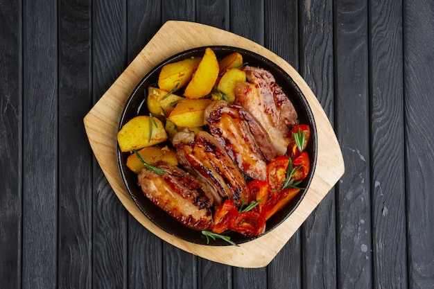 Gebratenes fleisch auf rippe mit kartoffeln und tomaten