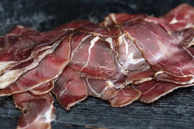 Gebratenes fleisch auf schwarzer oberfläche