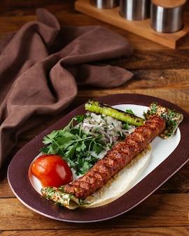Gebratenes fleisch einer vorderansicht mit zwiebelgrün und tomate auf dem braunen hölzernen schreibtischmahlzeitlebensmittelfleischessen