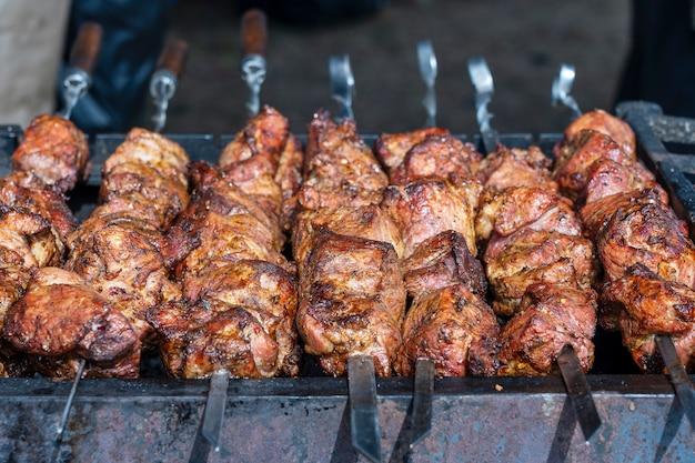 Gebratenes fleisch gekocht am grill. gegrillter kebab, der auf metallspieß kocht. bbq frisches rindfleisch hacken scheiben. traditionelles östliches gericht, schaschlik. grill auf holzkohle und flamme, streetfood, ukraine