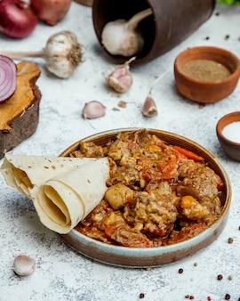 Gebratenes fleisch, kastanien und zwiebeln in einem ton versprechen mit fladenbrot