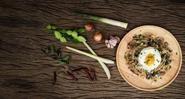 Gebratenes fleisch mit bambussprossen und heiligem basilikum, serviert mit gedämpftem reis-spiegelei